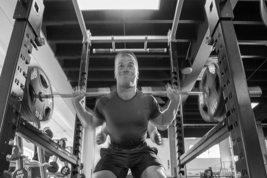 Barbell Squat weight training in the gym at Gravity Fitness And Tennis